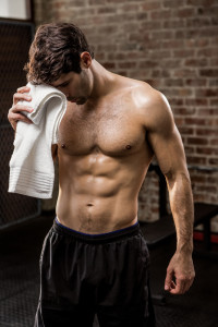 Muscular man wiping his face with towel at the gym